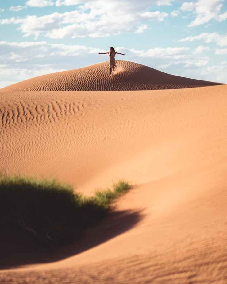 person standing on sand dunes